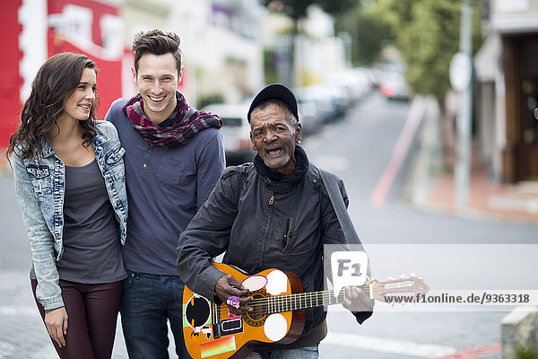 Young couple with guitar player on the street