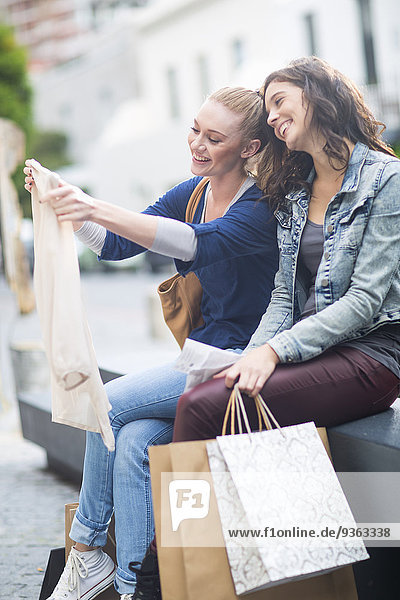 Two female friends watching their purchases