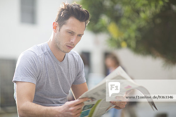 Portrait of young man reading newspaper