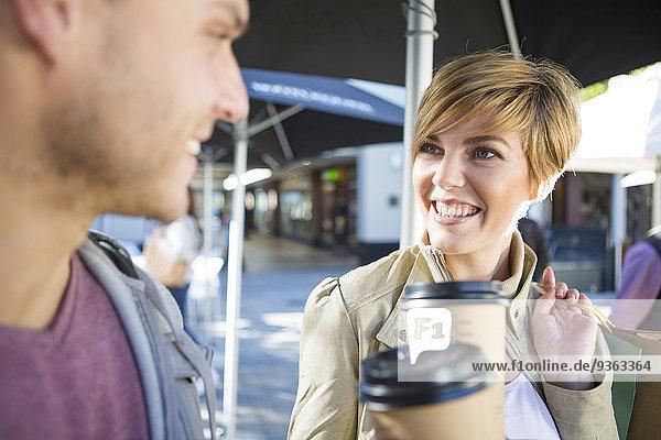 Lächelndes Paar mit Kaffee zum Mitnehmen