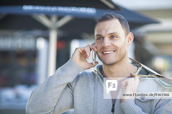 Porträt eines lächelnden Mannes mit Einkaufstaschen am Telefon