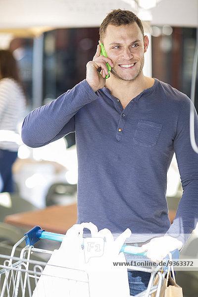Porträt eines lächelnden Mannes mit Taschen im Einkaufswagen beim Telefonieren