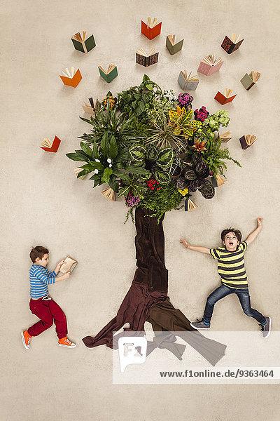 Kinder beobachten Bücher  die aus dem Baum fliegen