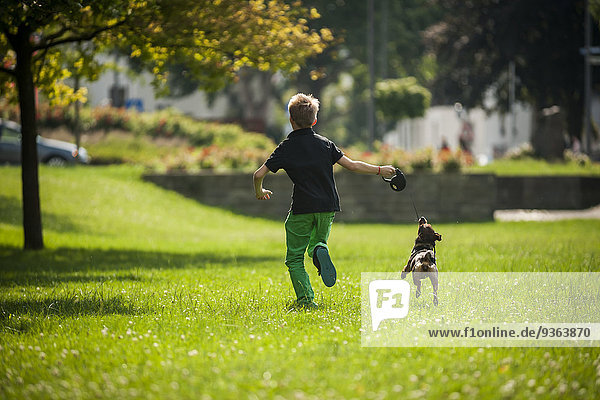 Junge rennt mit seinem Hund auf einer Wiese.