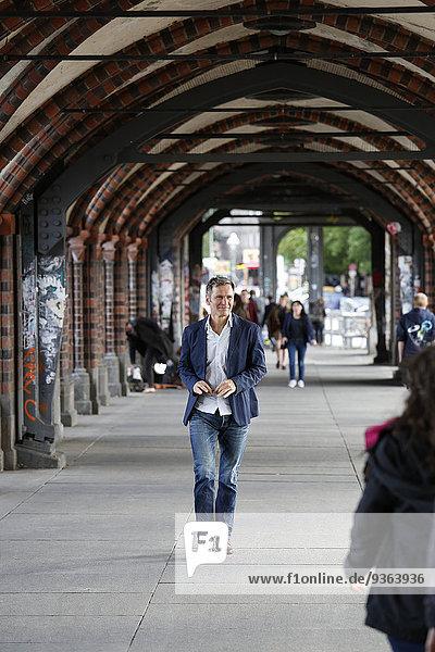 Deutschland  Berlin  Geschäftsmann zu Fuß in der Stadt