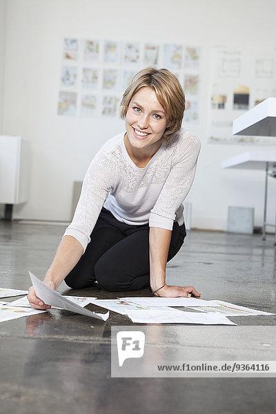 Porträt einer jungen Frau auf dem Boden eines Büros mit ihren Konzepten