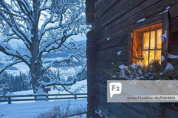 Österreich  Land Salzburg  Altenmarkt-Zauchensee  Holzkabinenfassade mit beleuchtetem Fenster im Winter