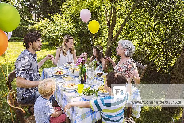 Familie von drei Generationen betend auf einer Gartenparty