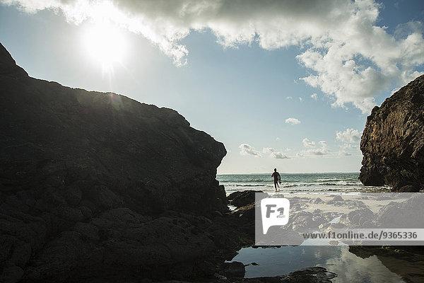Frankreich  Bretagne  Camaret-sur-Mer  Teenager mit Surfbrett am Meer