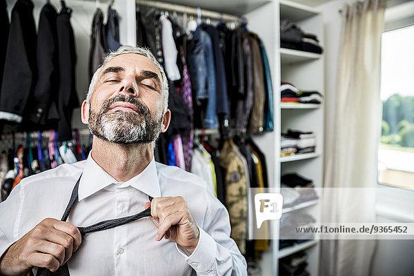 Geschäftsmann bindende Krawatte an seinem begehbaren Kleiderschrank