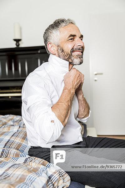 Porträt eines lächelnden Geschäftsmannes mit Krawatte im Schlafzimmer