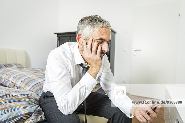 Businessman sitting on his bed looking at his smartphone