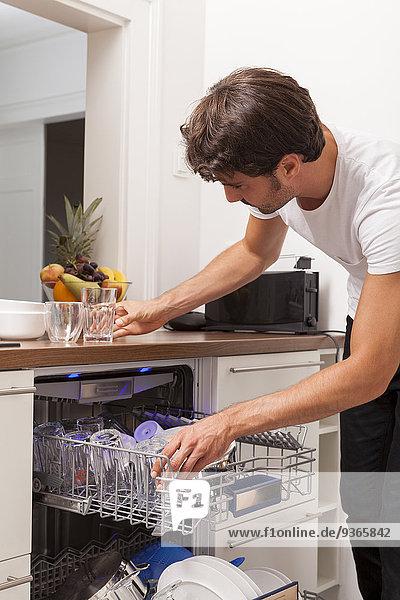 Lächelnder junger Mann beim Ausleeren der Spülmaschine