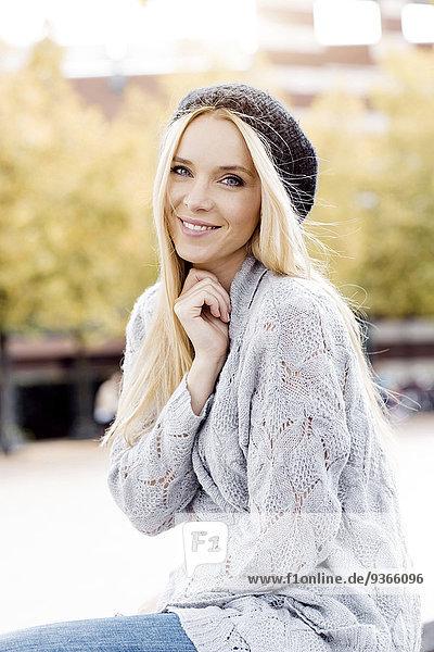 Porträt einer lächelnden jungen Frau mit Wollmütze und Strickjacke