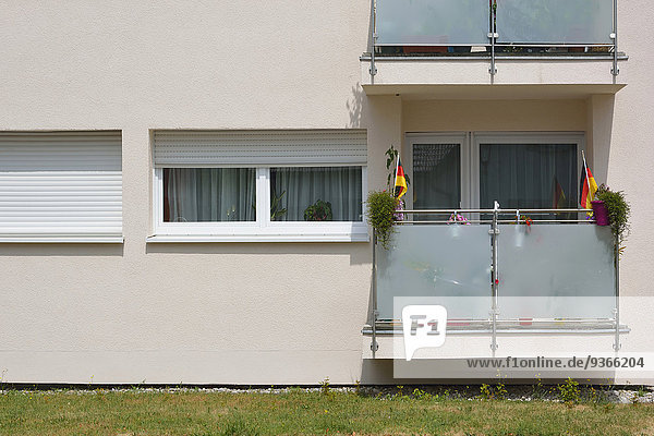Deutschland  Bayern  Balkon mit zwei Blumentöpfen und zwei kleinen deutschen Flaggen