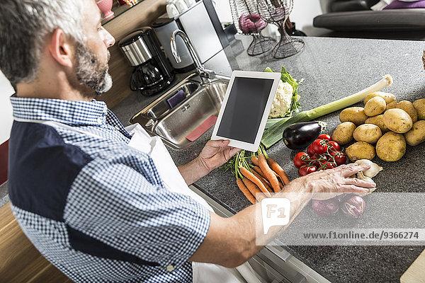 Österreich  Mann in der Küche mit digitaler Tablette zur Zubereitung von Speisen