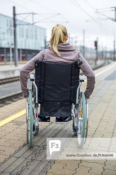 Frau im Rollstuhl am Bahnsteig wartend