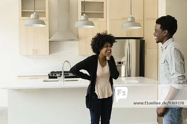 Couple talking in kitchen in new house