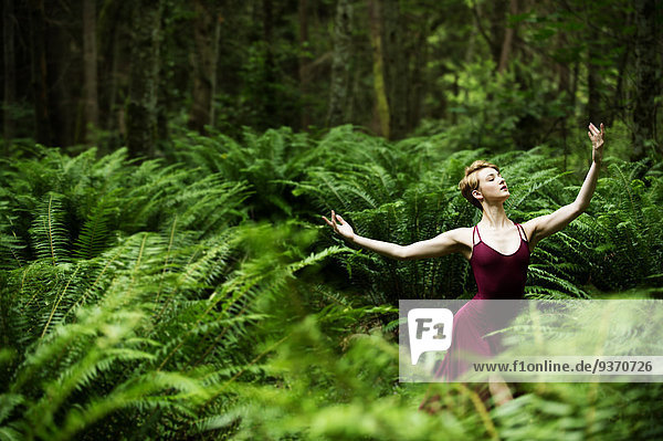 Caucasian woman dancing in forest