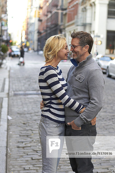 Caucasian couple hugging on city street  New York City  New York  United States