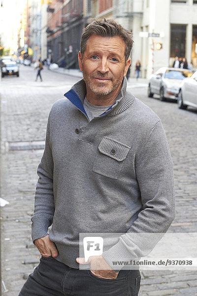 Caucasian man standing on city street  New York City  New York  United States