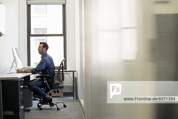 Büroalltag. Ein Mann in legerer Kleidung sitzt an einem Schreibtisch und schaut auf einen Computerbildschirm.