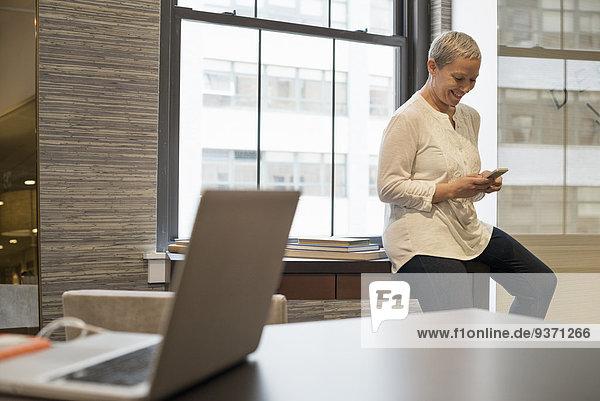 Büroalltag. Eine Frau sitzt an der Kante ihres Schreibtisches und benutzt ein digitales Tablett.