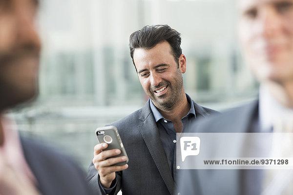 Drei Geschäftsmänner  einer überprüft sein Smartphone.