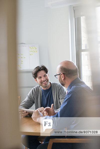 Zwei Geschäftskollegen in einem Büro  die sich unterhalten und sich auf ein digitales Tablet beziehen.