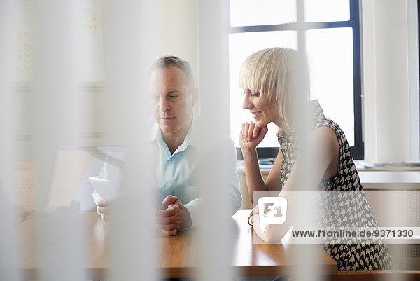 Zwei Geschäftskollegen in einem Büro  die sich unterhalten und sich auf einen Computerbildschirm beziehen.