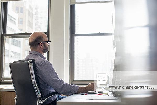 Büroalltag. Ein Mann sitzt an einem Schreibtisch mit einem Computer und schaut aufmerksam auf den Bildschirm.