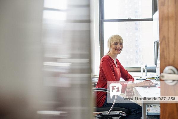 Büroalltag. Eine Frau sitzt an einem Schreibtisch  schaut in die Kamera und lächelt.