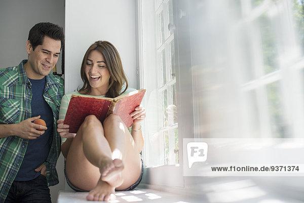 Frau  die am Fenster sitzt und ein Buch liest. Ein Mann steht neben ihr und isst einen Apfel.