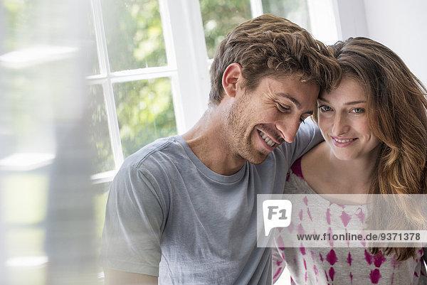 Paar  das sich durch ein Fenster umarmt.