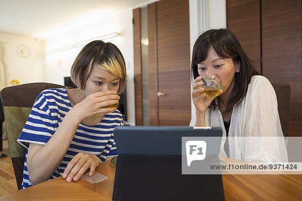 Eine Frau sitzt an einem Tisch mit einem Laptop-Computer.