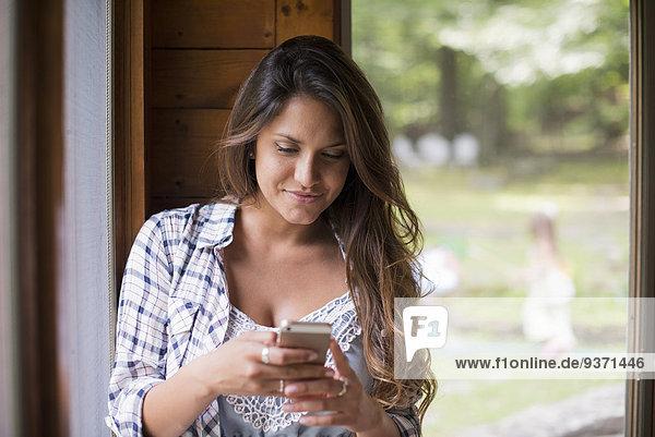 Eine Frau sitzt an einem Fenster und schaut auf ihr Handy.