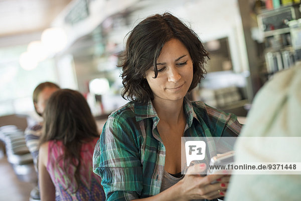 Eine Frau in einem Diner  die auf ihr Handy schaut.