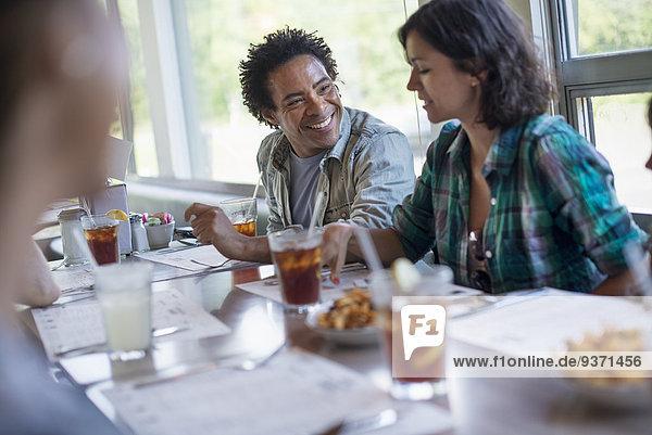Eine Gruppe von Freunden beim Essen in einem Diner. Ein Paar  das nebeneinander sitzt.