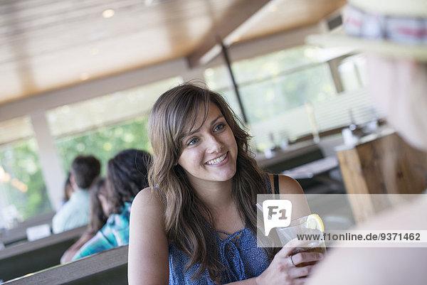 Eine junge Frau sitzt an einem Tisch in einem Diner mit einem kühlen Getränk.