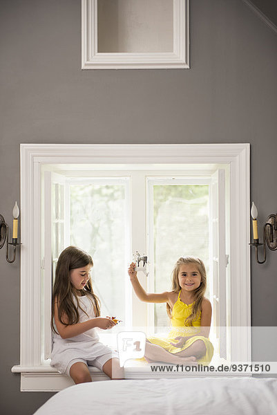 Two girls playing together  sitting on a window seat indoors.
