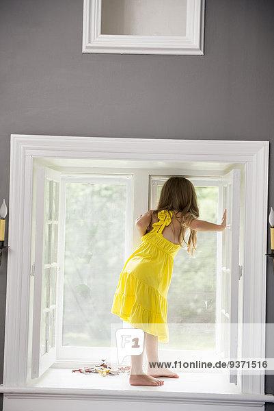 Ein Mädchen in einem weißen Kleid  das an einem Fenster sitzt und spielt.