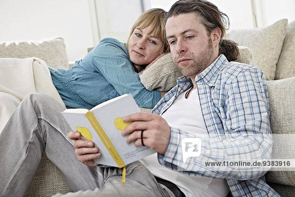 Couple On Sofa  Man Reading Book