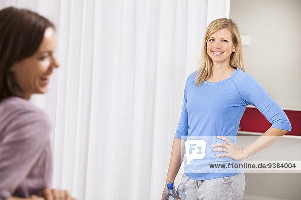 Two women taking a break from fitness training in gym