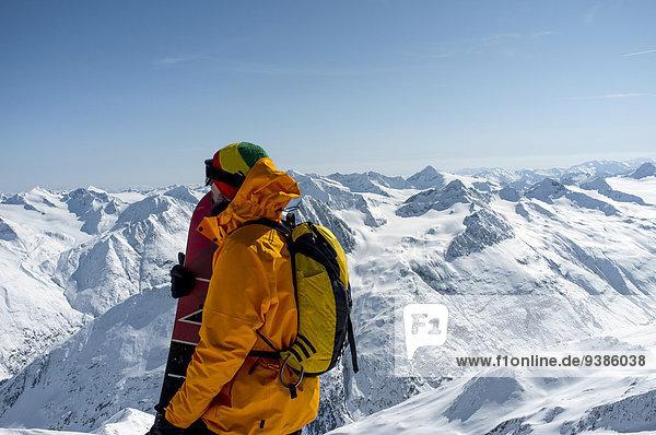 Back country skier taking a look at mountain range  European Alps  Tyrol  Austria