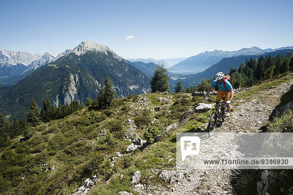 Mountain biker riding on Alpine trail  Tyrol  Austria