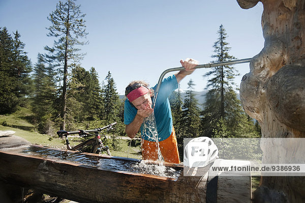 Mountain biker drinking water at standpost  Tyrol  Austria