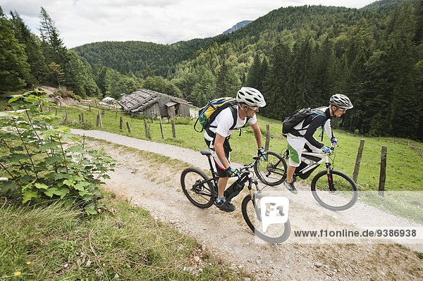 Two mountain bikers riding on a trail  pasture in background  Chiemgau  Bavaria  Germany