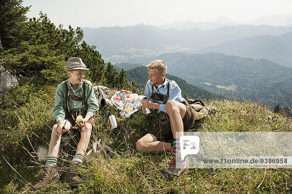 Germany  Bavaria  Two boys in traditional clothing taking a rest in mountains