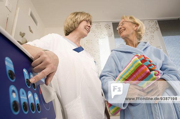 Senior woman and nurse preparing for hydrotherapy  Bavaria  Germany