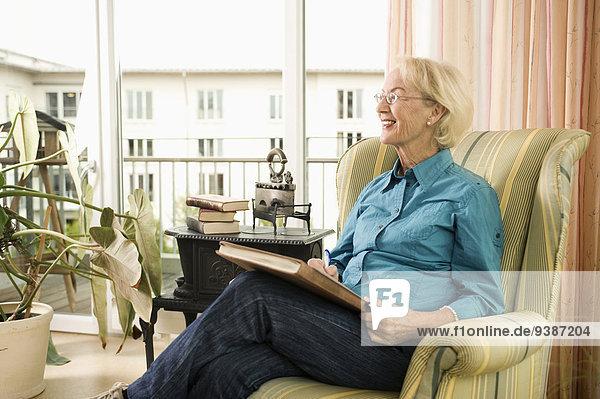 Senior Senioren Frau sitzend Buch Sessel Taschenbuch